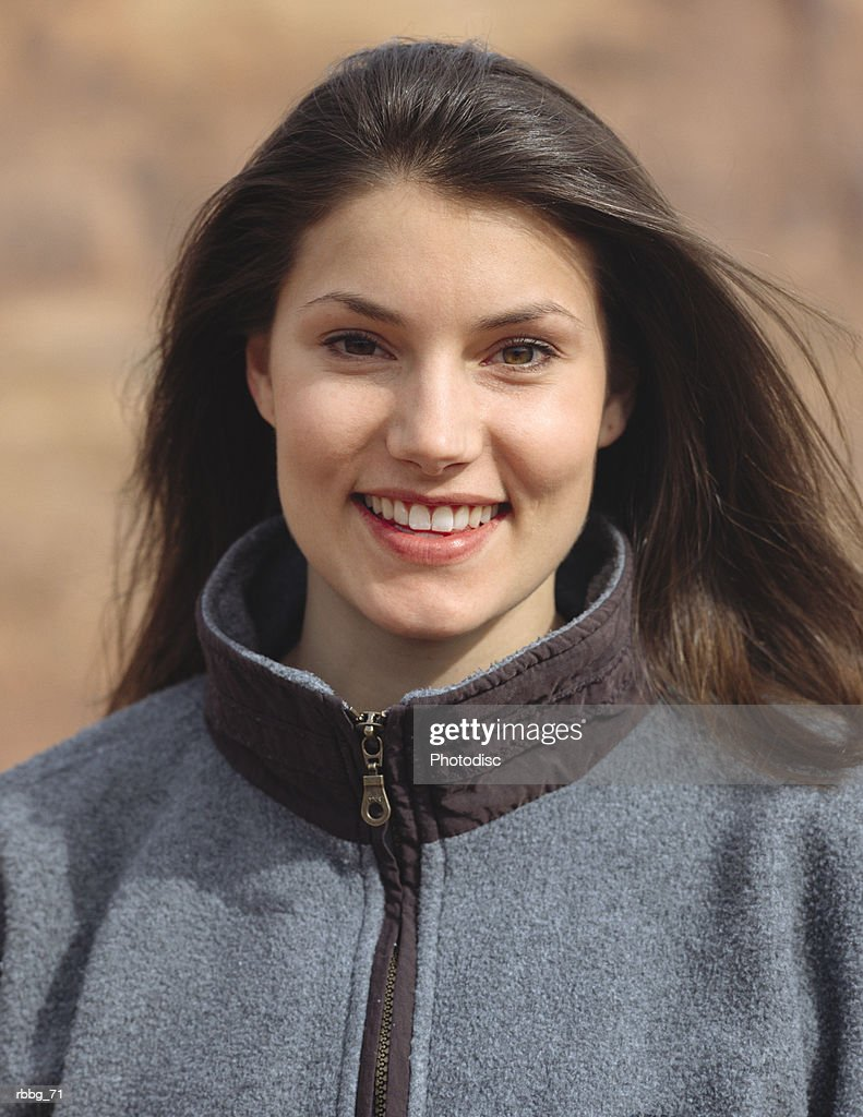 happy beautiful brown haired woman smiling standing in red rock country of Moab Utah : Stockfoto