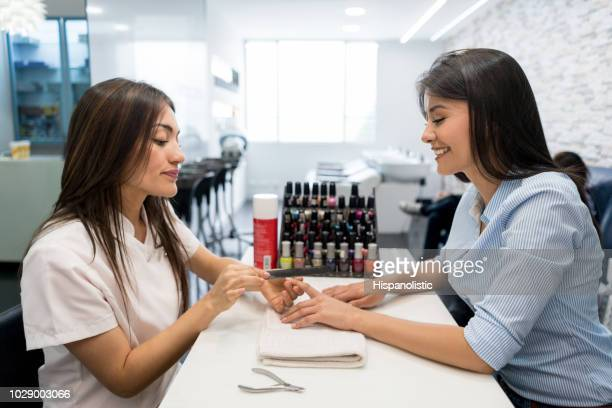 happy beautiful customer enjoying getting a manicure at a nail salon - nail salon stock pictures, royalty-free photos & images