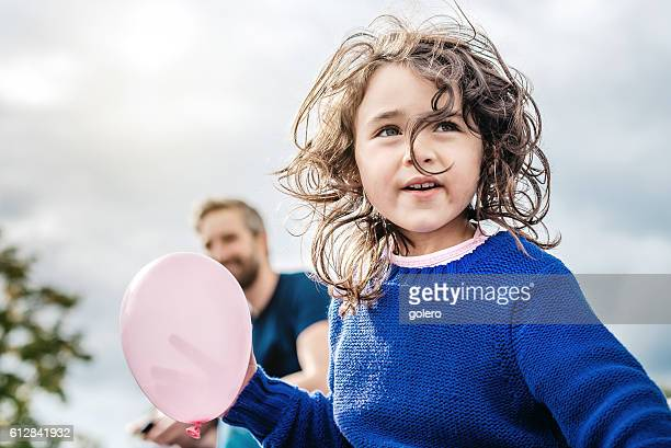 happy beautiful little girl with pink  balloon looking