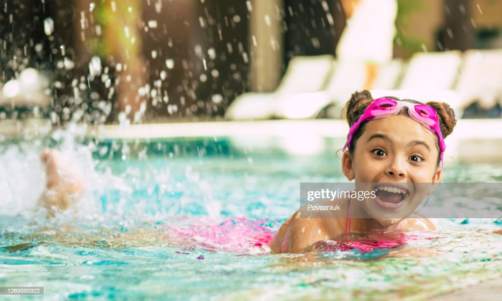 Happy beautiful little smiling girl in goggles and swimsuit in the pool has fun while vacationing or swimming lessons. : Stock Photo