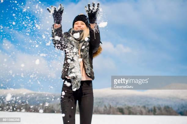 Happy Beautiful Teenaged Woman Throwing a Snowball