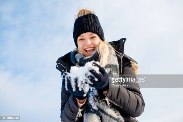 Happy Beautiful Teenaged Woman with Snowball in Hands