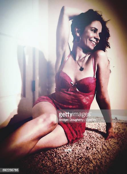 Happy Beautiful Woman In Lingerie Sitting On Rug At Home