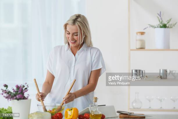 Happy beautiful woman listening music and tossing salad in bowl at kitchen counter against wall