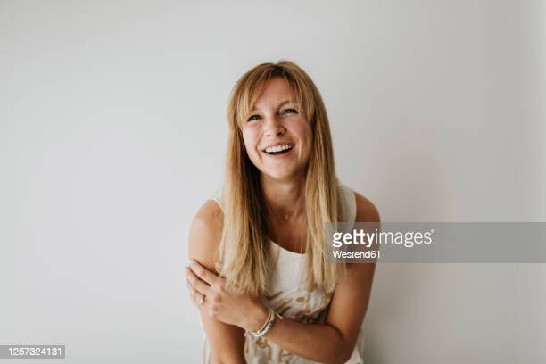 happy beautiful woman standing against white wall at home - sleeveless stock pictures, royalty-free photos & images