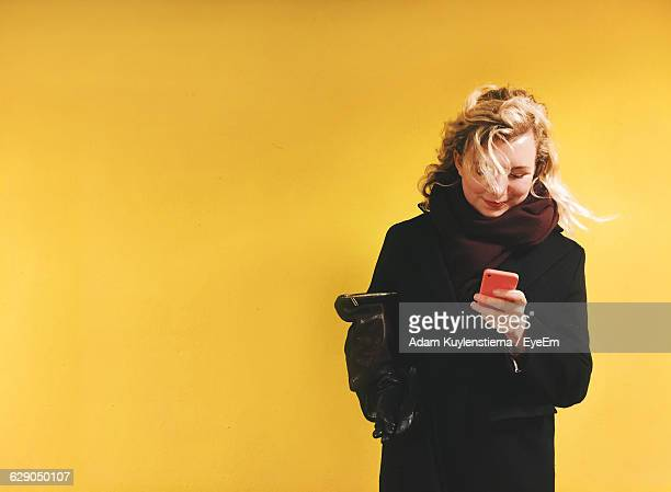 happy beautiful woman using phone against yellow background - eine person stock-fotos und bilder