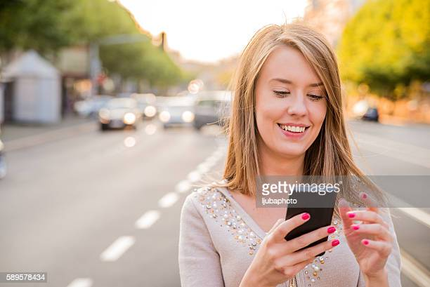 Happy beautiful woman walking and writing or reading sms message