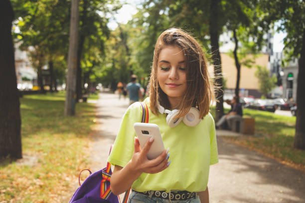 Happy beautiful young high school girl with white smart phone