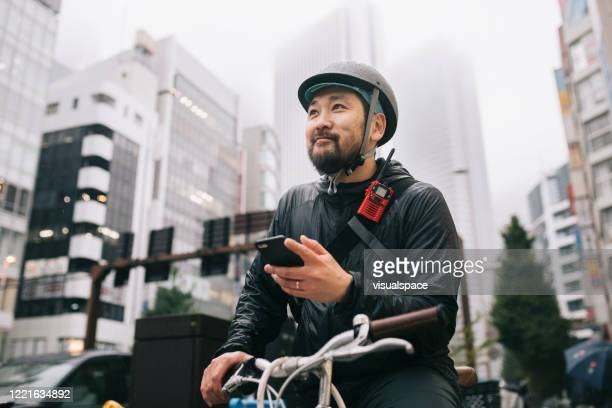 happy bike messenger - japan stock pictures, royalty-free photos & images