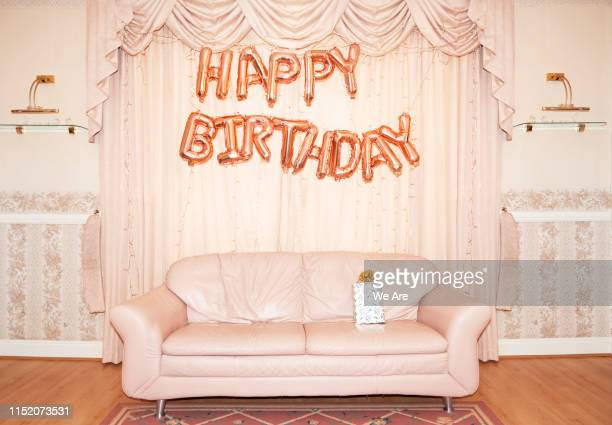 happy birthday balloons hanging above sofa in living room - happy birthday stock pictures, royalty-free photos & images
