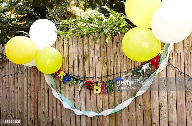 happy birthday banner and balloons tied to fence - birthday balloons stock photos and pictures