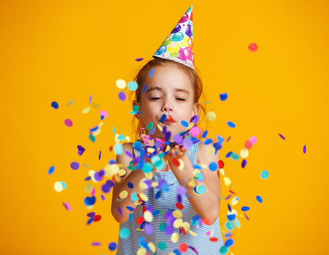 happy birthday child girl with confetti on yellow background 1126992132