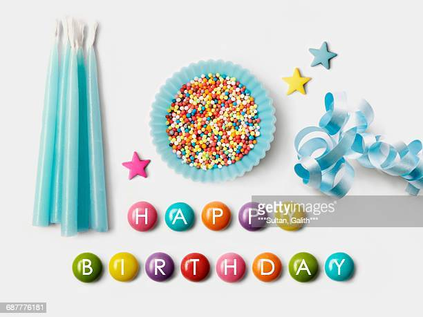 Happy Birthday written on Smarties and a blue paper cup full of sugar balls for decorating cakes,ribbon and blue birthday candles