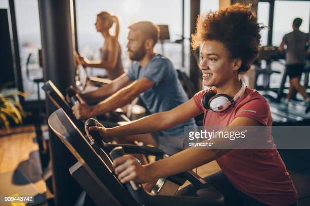 Happy black athlete practicing on exercise bike in a health club.