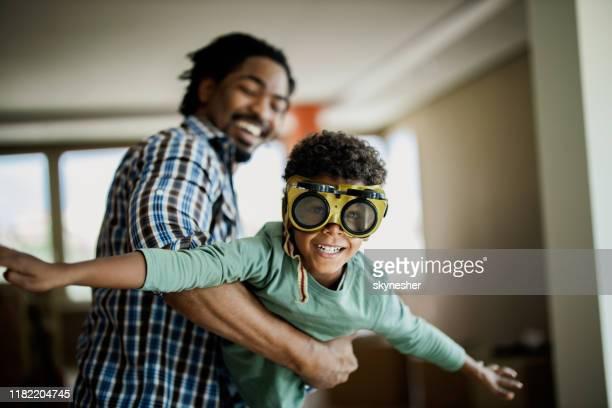 menino preto feliz que tem o divertimento com seu pai em casa. - brincar - fotografias e filmes do acervo