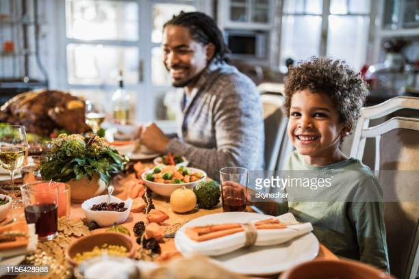happy black boy having thanksgiving meal with his father at dining table. - kids thanksgiving stock pictures, royalty-free photos & images