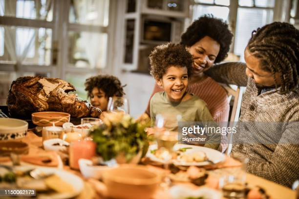 happy black boy talking to his parents during thanksgiving dinner at dining table. - thanksgiving holiday stock pictures, royalty-free photos & images