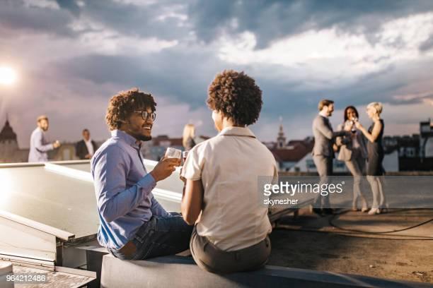 Glücklich schwarze Geschäftsmann Toasten mit seinem Kollegen auf einer Party auf dem Dach.