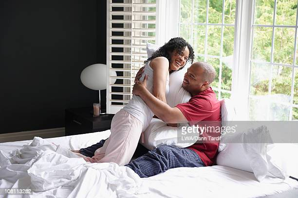 Happy Black couple playing in bed