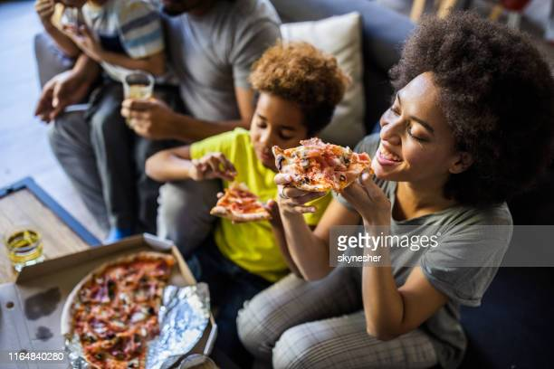 happy black family having pizza for lunch at home. - pizza stock pictures, royalty-free photos & images