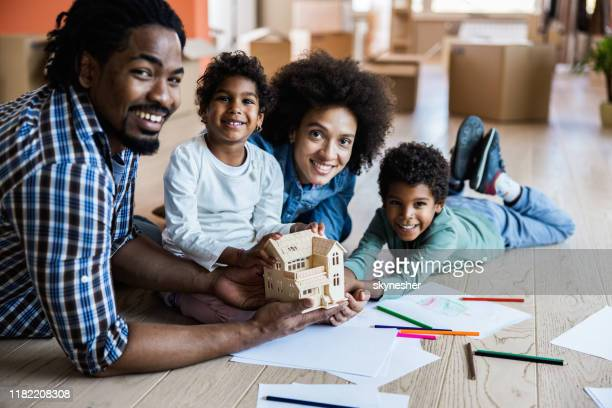 happy black family holding model house during home relocation. - model home stock pictures, royalty-free photos & images