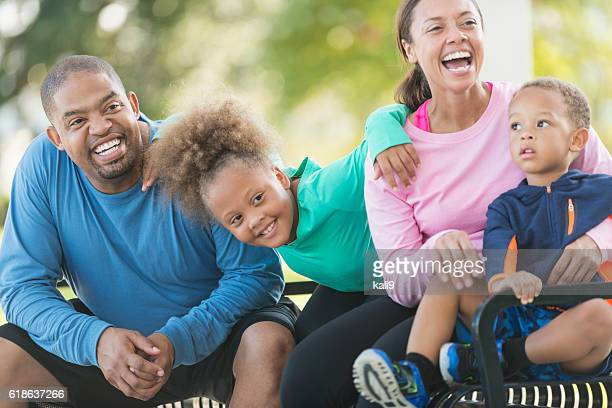 Happy black family sitting on park bench laughing