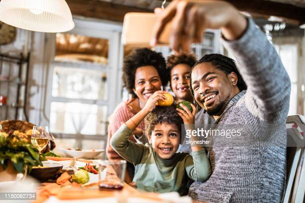 happy black family taking a selfie with cell phone in dining room. - thanksgiving holiday stock pictures, royalty-free photos & images