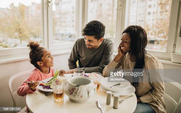 Happy black family talking during lunch in the kitchen.