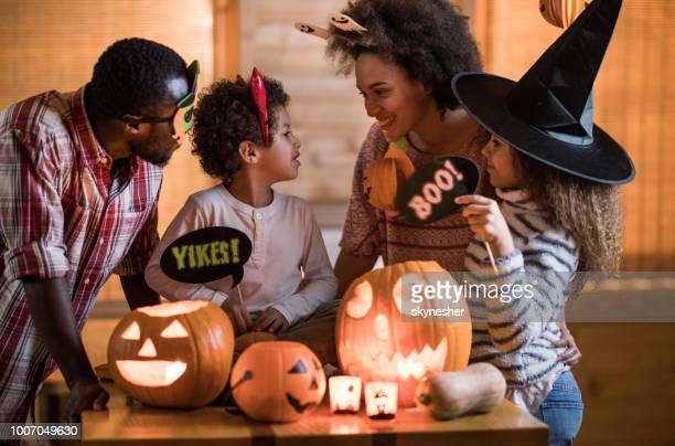 happy black family talking while enjoying in halloween at home. - happy halloween stock photos and pictures