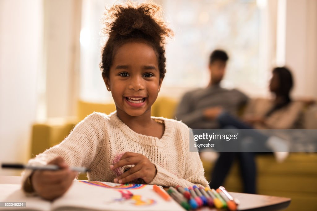 Happy black girl having fun while drawing and looking at camera. : Stock Photo