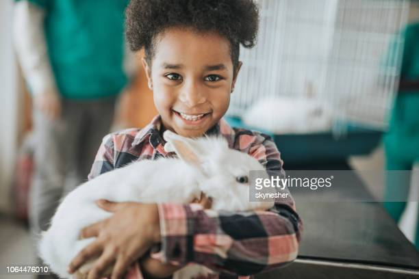 happy black girl with her rabbit at vet's hospital. - rabbit animal stock pictures, royalty-free photos & images
