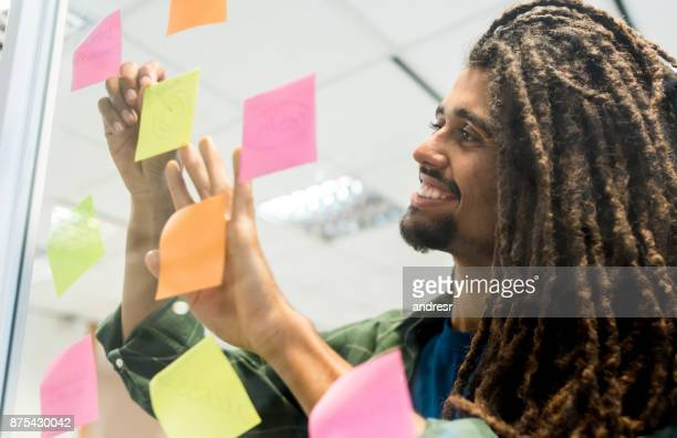 Happy black man adding ideas and brainstorming at the office on adhesive notes smiling