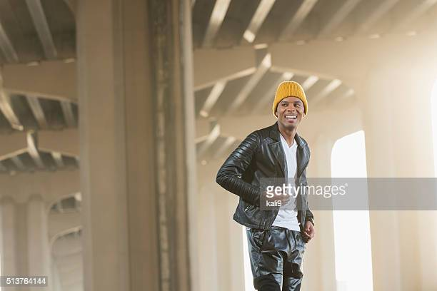 happy black man wearing yellow beanie, leather jacket - all hip hop models stock photos and pictures