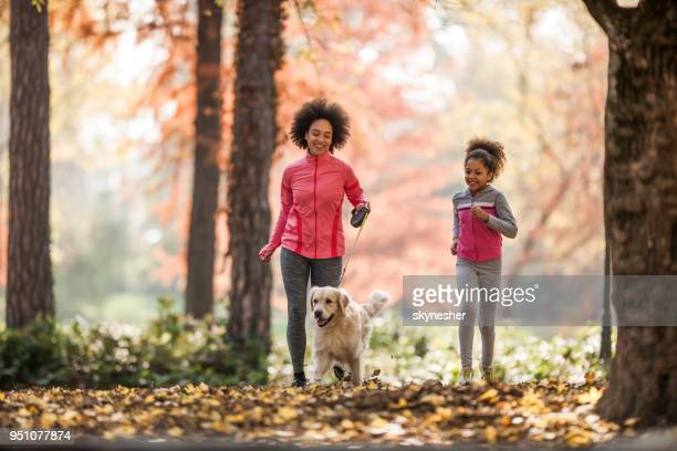 happy black mother and daughter jogging with a dog in autumn day. - autumn dog stock pictures, royalty-free photos & images