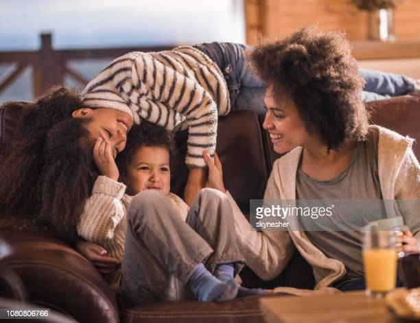 Happy black mother having fun with her small kids at home.