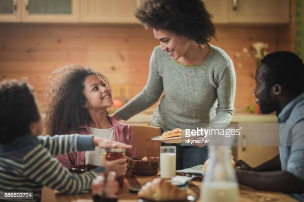 Happy black mother serving food to her family in dining room.