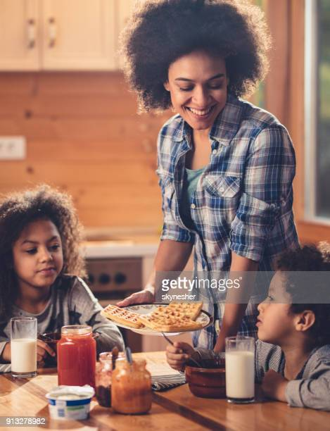 happy black mother serving her kids belgian waffles for breakfast. - waffle stock pictures, royalty-free photos & images