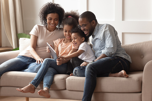 Happy black parents and children using digital tablet on sofa 1158481678