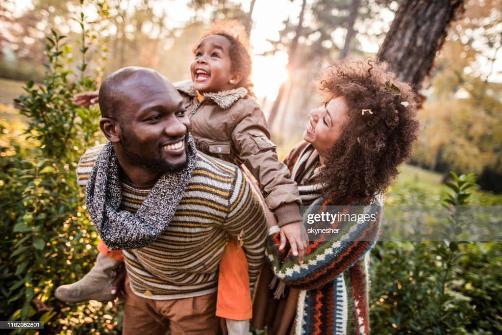Happy black parents having fun with their daughter at the park. : Stock Photo