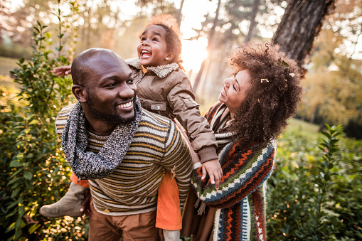 Happy black parents having fun with their daughter at the park. 1162082801