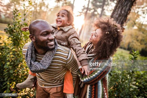 happy black parents having fun with their daughter at the park. - família imagens e fotografias de stock