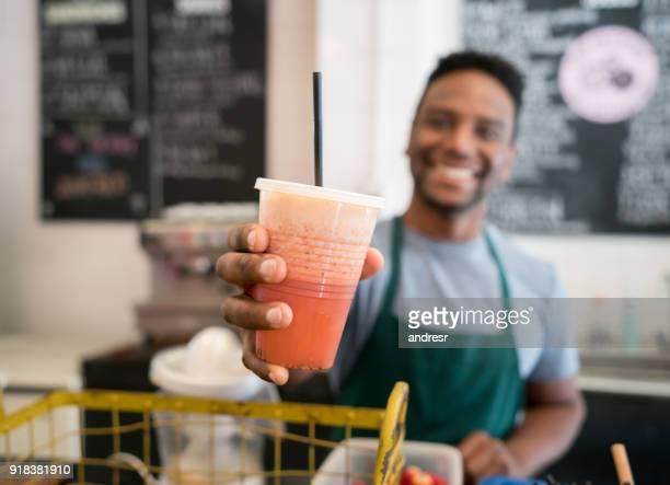 Happy black salesman handing a strawberry juice looking at camera smiling