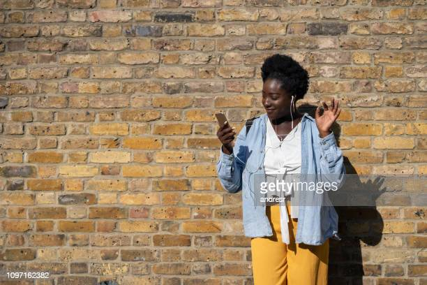 happy black woman listening to music with headphones on the street - upload stock pictures, royalty-free photos & images