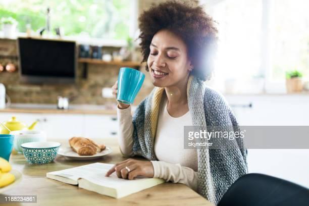 glückliche schwarze frau lesen ein buch während morgendlichen kaffee zu hause. - junge frau allein stock-fotos und bilder