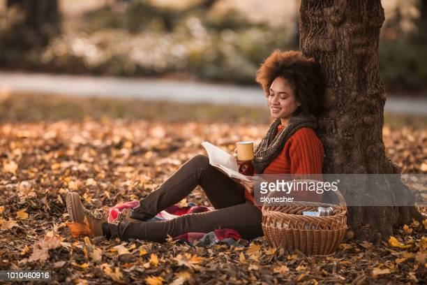 happy black woman reading a book while enjoying on picnic in autumn day. - autumn stock pictures, royalty-free photos & images
