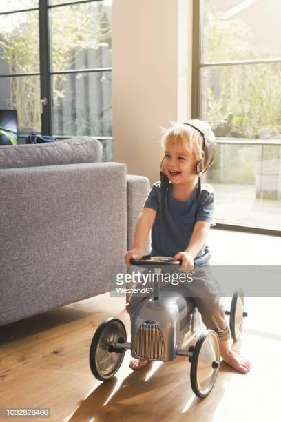 Happy blond boy playing on toy car