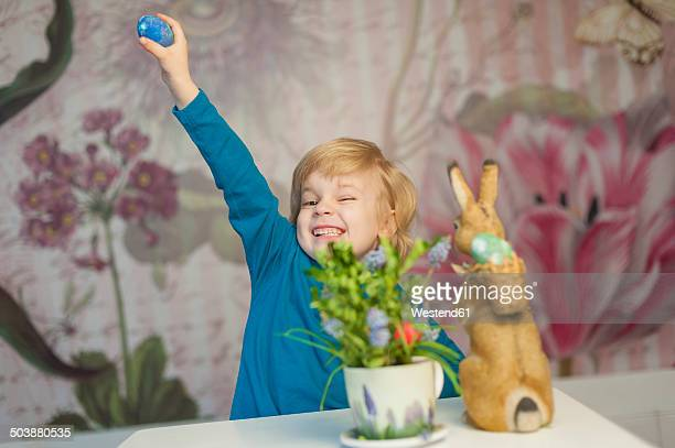Happy blond boy with Easter bunny holding egg