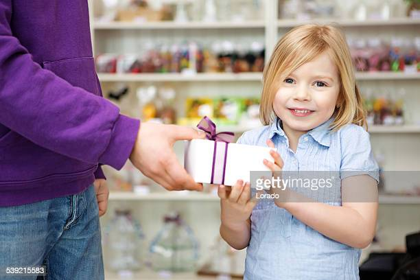 happy blond girl receiving gift in candy shop