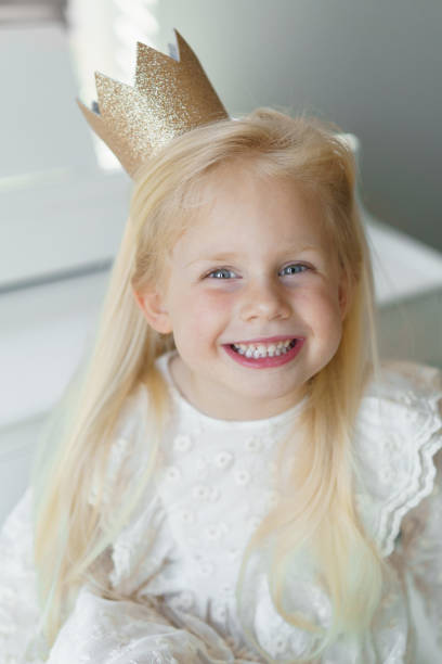 Happy blond girl smiling wearing golden crown.