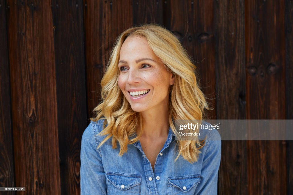 Happy blond woman in front of wooden wall : Stock Photo